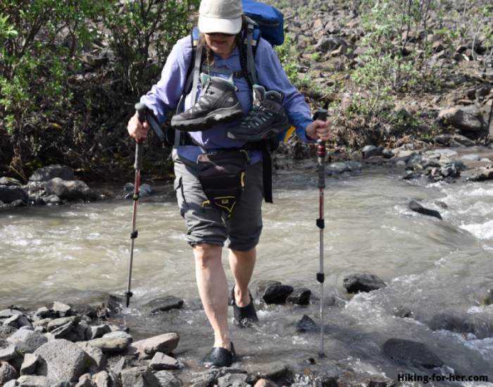Female backpacker crossing a river, with boots around her neck, using trekking poles and river shoes