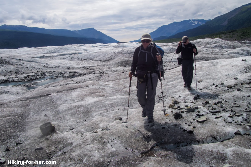 Male and female hikers exploring surface of glacier