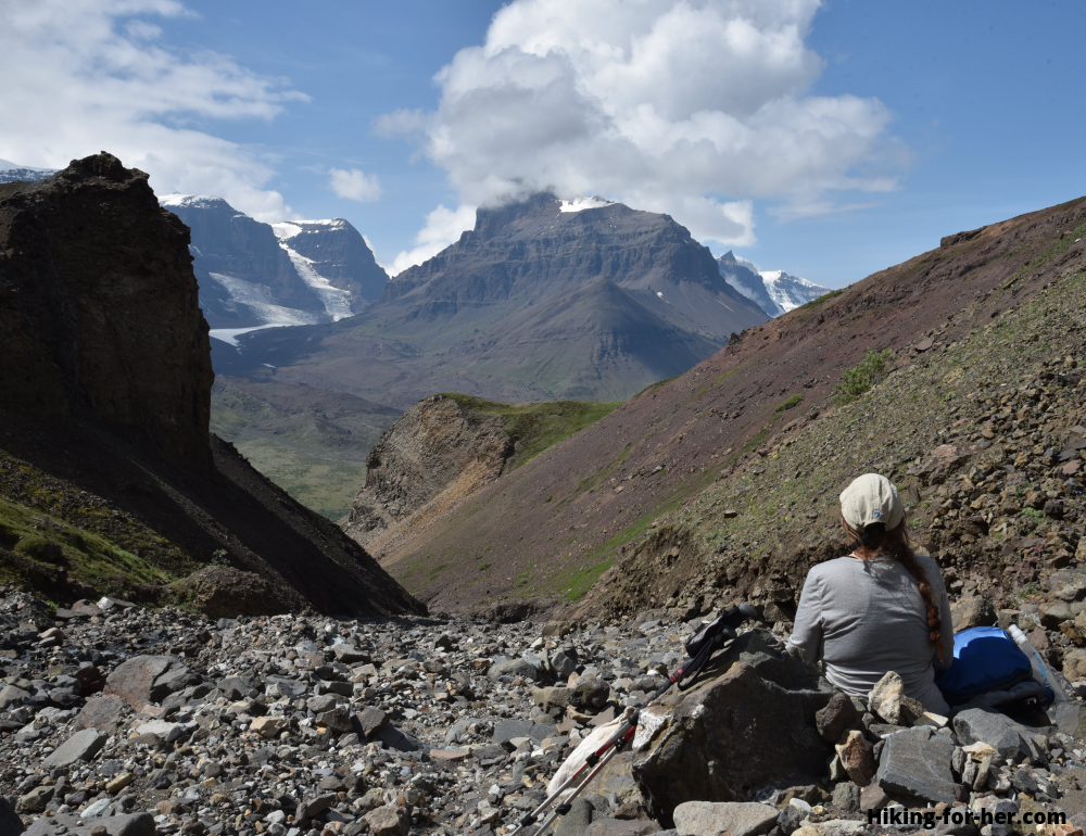 Female hiker in rugged terrain admiring glaciers and mountains in Wrangell St Elias National Park and Preserve in Alaska (Skolai)