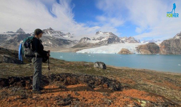 Female hiker wearing backpack and holding trekking poles while gazing at glacier in Greenland