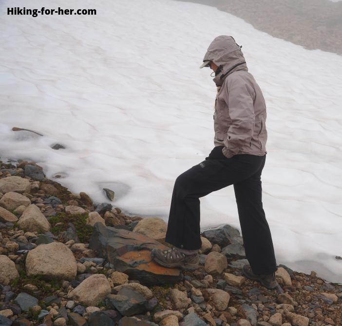Female hiker in rain gear walking up rocky slope at edge of ice field
