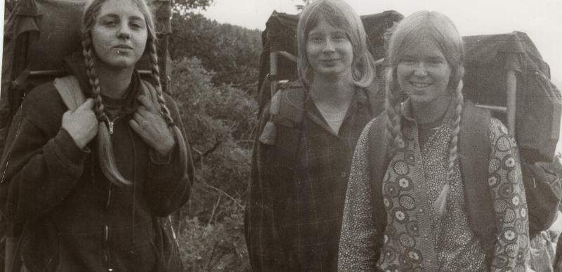Three teenage girls with external frame backpacks in a black and white photo