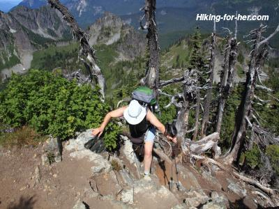 Female hiker wearing a white hat and green backpack as she climbs a steep trail using her hands and hiking poles