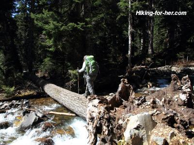 Female hiker wearing green backpack crossing a log over a rushing stream