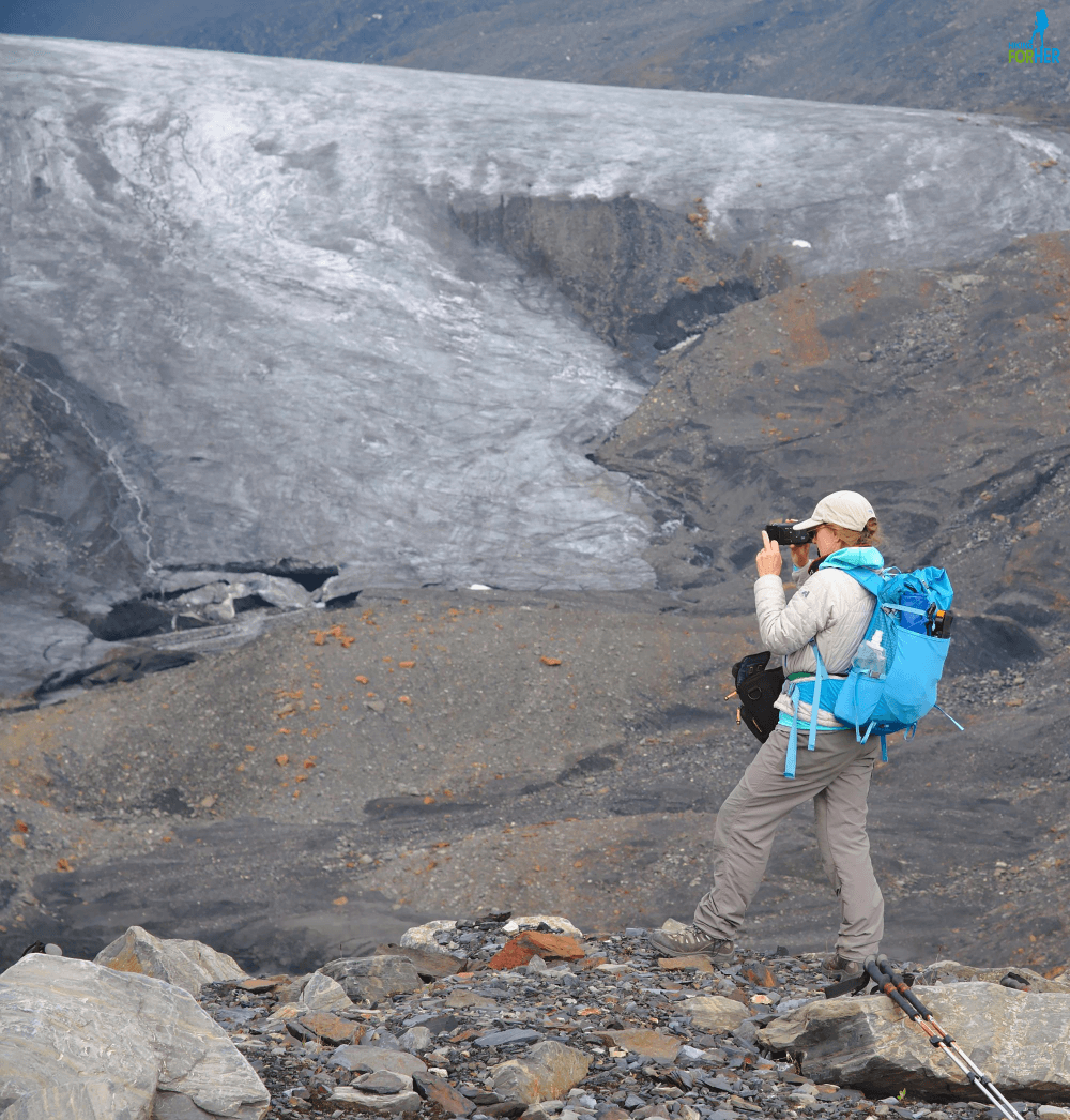 Female hiker taking a photograph, wearing technical hiking clothing and backpack