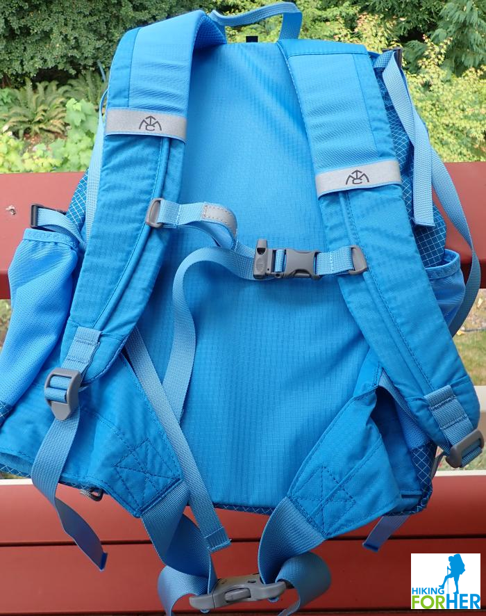 Women's blue hiking day pack from the back, showing shoulder straps, sternum belt, side pockets and haul strap
