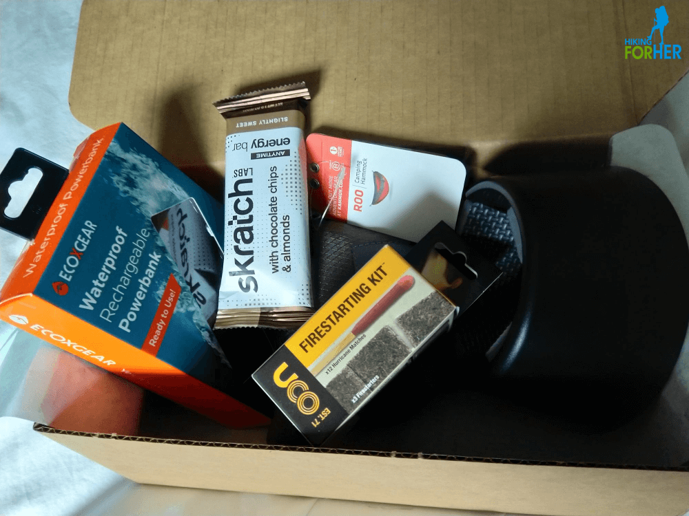 The Nomadik subscription outdoor gear box contents, including a charger, fire starter kit, trail snack, tote bag and mug holder