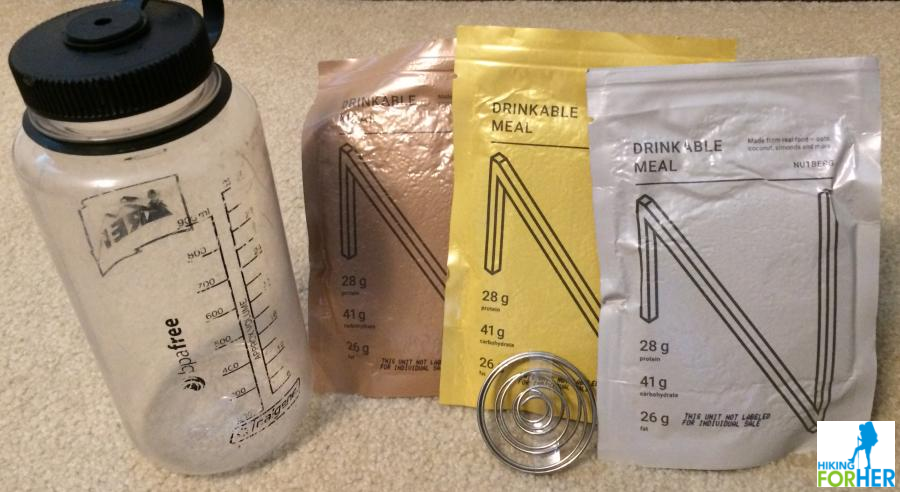 Clear Nalgene wide mouth water bottle and 3 packets of Nutberg, plus a metal coiled agitator to break up clumps