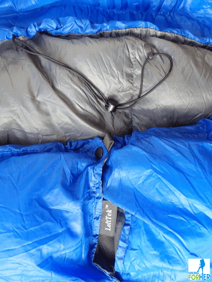 Blue and gray ultralight backpacking quilt close up of the top pull cord and snaps