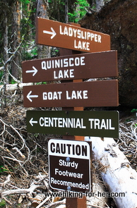 Hiking trail signs pointing to lakes and ridges, cautioning that sturdy footwear is recommended