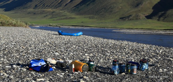 Bear cannisters and kitchen on gravel bar of a river