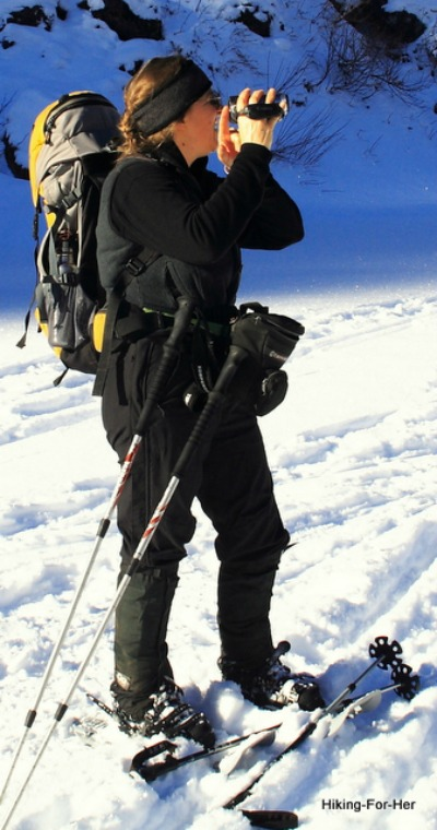 Female snowshoer wearing yellow and gray backpack, taking a photo