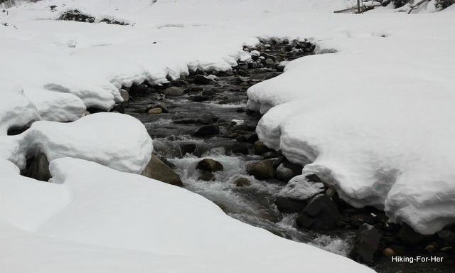 Icy rock filled creek flowing through snow covered banks