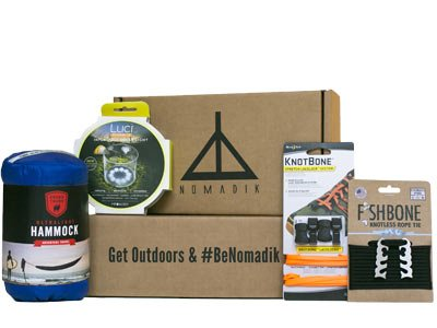 The Nomadik subscription box with logo and examples of outdoor gear